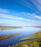 Landschaft mit Fluss und großen Wolken Stockbilder