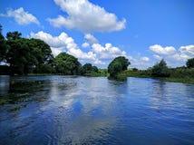 Landschaft mit Fluss und Wolken Stockbild