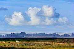 Landschaft mit Landstraße und isländischem Gebirgszug Stockfotografie