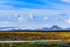 Landschaft mit Landstraße und isländischem Gebirgszug Stockbild