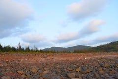 Landschaft mit Rocky Land, entfernte Berge, Wolken im blauen Himmel - natürlicher Hintergrund Lizenzfreie Stockfotografie