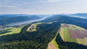 Landschaft mit See, Hügeln und Ackerland Brummenansicht von oben Lizenzfreie Stockfotos