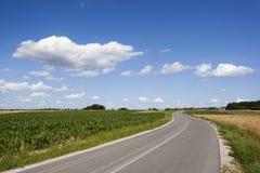 Landschaft mit Straße und einem blauen Himmel Lizenzfreies Stockbild