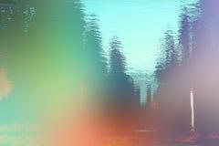 Landschaft reflektiert im Wasser Feld des grünen Grases gegen einen blauen Himmel mit wispy weißen Wolken Lizenzfreie Stockfotos