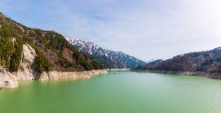 Landschaft von Bergen mit grünem See an Kurobe-Verdammung Lizenzfreie Stockfotos
