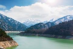 Landschaft von Bergen mit grünem See an Kurobe-Verdammung Lizenzfreies Stockfoto