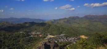 Landschaft von den Bäumen, die schöne Stadt und Berge übersehen Lizenzfreie Stockbilder