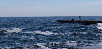 Landschaft von Meer mit einer Zahl eines Mannes Lizenzfreie Stockfotos