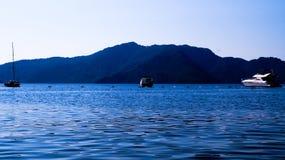 Landschaft von Meer und von Bergen mit 3 Booten Lizenzfreie Stockfotos