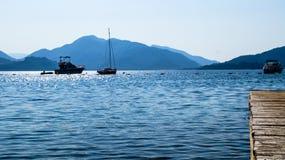 Landschaft von Meer und von Bergen mit den Booten und der Anlegestelle Lizenzfreie Stockfotos