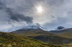 Landschaft von schneebedeckten Bergen und von bew?lktem Himmel in Norwegen im Sommer lizenzfreie stockbilder