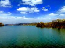 Landschaft von See mit Himmel, Wolken und Wald stockfotos