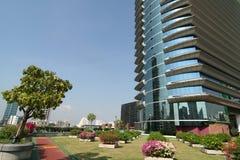 Landschaftlich verschönerter Garten unter modernem Wolkenkratzer Lizenzfreie Stockfotos