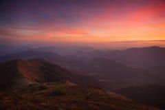 Landschaftsabend-Herbstberge bei Sonnenuntergang Ein Blick von der Spitze der Hügel Lizenzfreies Stockfoto