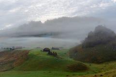 Landschaftsansicht ?ber ikonenhaftes Haus und den Baum bedeckt im Nebel bei Fundatura Ponorului, Rum?nien stockfotografie