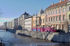 Landschaftsbild von Stadtflussbänken mit Gebäuden und von Brücke in der Ansicht Lizenzfreie Stockbilder