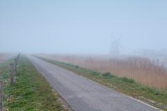 Landschaftsfahrradstraße und -windmühle im Nebel Lizenzfreie Stockbilder