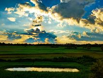 Landschaftsfoto des Sonnenlichts zerstreuend durch die Wolken über einem Teich lizenzfreie stockbilder