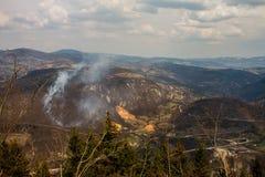 Landschaftsfrühlings-Wald und Feld, die mit blauen Bergen und herrlichem epischem Himmel mit Wolken oben brennen stockfotografie