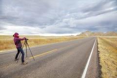 Landschaftsphotograph macht Fotos auf einer leeren Straße Lizenzfreie Stockbilder