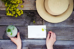 Landschaftsreise und Ferienhintergrund Weibliche Hände, die Postkarte umgeben mit Glas Limonade, Strohhut, Wildflower halten Stockfoto