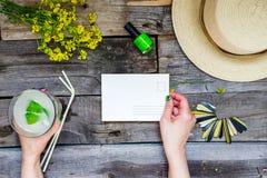 Landschaftsreise und Ferienhintergrund Weibliche Hände, die Postkarte umgeben mit Glas Limonade, Strohhut, Wildflower halten Lizenzfreie Stockfotos