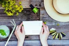Landschaftsreise und Ferienhintergrund Weibliche Hände, die Postkarte umgeben mit Glas Limonade, Strohhut, Wildflower halten Lizenzfreies Stockbild