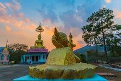 Landschaftssonnenuntergang hinter dem goldenen Buddha in Chiang Rai stockbilder
