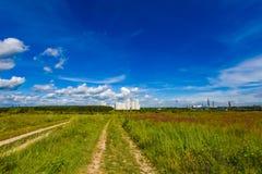 Landschaftsstraßenfußweg durch ein Feld Stockbild