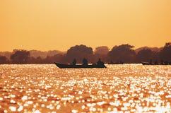 Landschap bij zonsondergang van boten met vissers die op Pantanal vissen stock foto