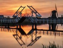 Landschap dat van een brug en een windmolen in een oranje zonsondergang wordt geschoten royalty-vrije stock foto