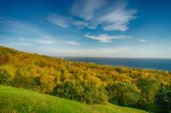 Landschap die die de helling overzien met bomen en een grote rivier, blauwe hemel wordt behandeld De vroege herfst stock fotografie