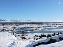 Landschap IJsland van het Pingvellir het Nationale Park Water, bergen, sneeuw en weg Stock Afbeelding