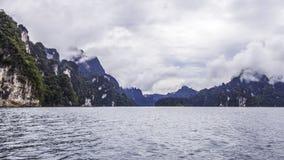Landschap met achtergrondbergenbomen en mist en een meer in voorzijde, die na zware regenachtige dag gelijk maken Slechte verlich Stock Afbeeldingen