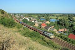 Landschap met de trein, het dorp en de rivier royalty-vrije stock foto's