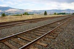 Landschap met een spoorwegspoor en bergen op de achtergrond Stock Foto