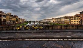 Landschap met gele fietsen Weergeven van de rivier Arno Florence Italië stock afbeelding