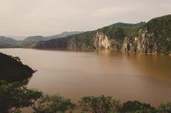Landschap met inbegrip van kalm bruin water van Meer Nyos, beroemd voor Co2-uitbarsting met vele sterfgevallen, Ring Road, Kamero royalty-vrije stock afbeelding