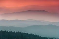 Landschap met kleurrijke die lagen bergen en nevelheuvels door bos worden behandeld stock fotografie