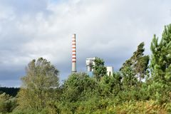 Landschap met krachtcentrale Lange rokende schoorsteen, bomengras en struiken Bewolkte dag, grijze hemel, aard en de industrie stock foto's