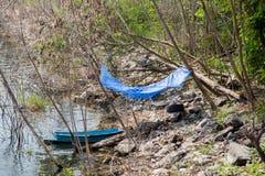 Landschap met oude houten het roeien blauwe boten die op riverbank landen Stock Foto's