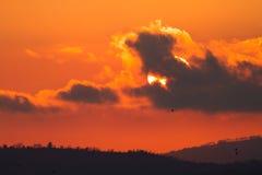 Landschap met rode zon die achter donker wolken en silhouet plaatsen Royalty-vrije Stock Foto's