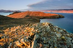 Landschap met rots en meer op zonsondergangachtergrond Stock Fotografie