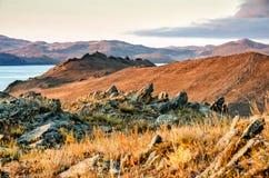 Landschap met rots en meer op zonsondergangachtergrond Royalty-vrije Stock Foto
