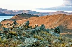 Landschap met rots en meer op zonsondergangachtergrond Royalty-vrije Stock Afbeelding