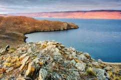 Landschap met rots en meer op zonsondergangachtergrond Stock Afbeeldingen