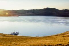 Landschap met schip en meer op zonsopgangachtergrond Royalty-vrije Stock Foto