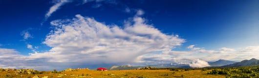 Landschap met stormachtige hemel en huis in bergen stock foto
