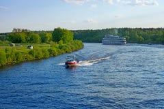 Landschap met Volga rivier, motorboot en cruiseschip op een som Stock Afbeeldingen