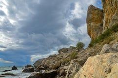 Landschap op een rotsachtig overzees strand met een schilderachtige hemel, de Krim, Sudak Royalty-vrije Stock Afbeeldingen